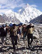 Transportando el cuerpo de Sher Ajman glaciar abajo. Al fondo, vertiente sur del K2 - Foto: Exp. Española K2 2002