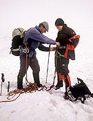 Un guía de montaña encordándose a su cliente. ~ desnivelpress.com