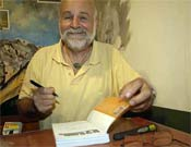 """El alpinista austriaco Kurt Diemberger firmando ejemplares durante la presentación de su libro """"K2. El nudo infinito"""" en la Librería Desnivel el 26 de septiembre de 2005.<br>Foto: Desnivelpress"""