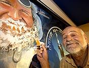 Diemberger firma su retrato en el mural de la Librería Desnivel.- Foto: Desnivelpress